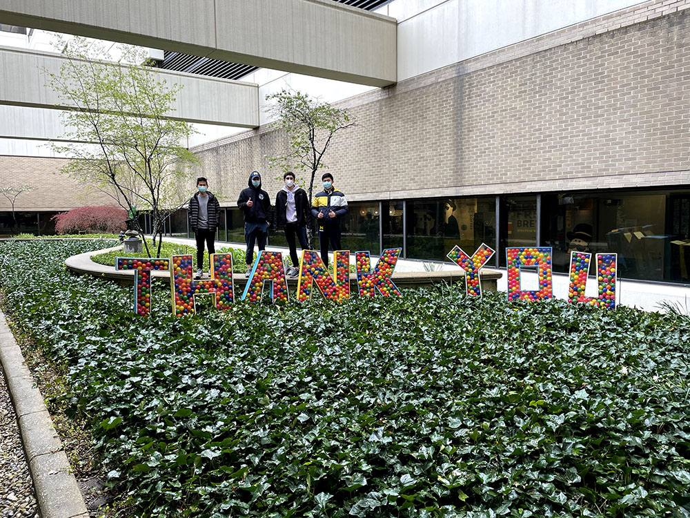 Four students in masks standing behind letters spelling out THANK YOU in a courtyard.