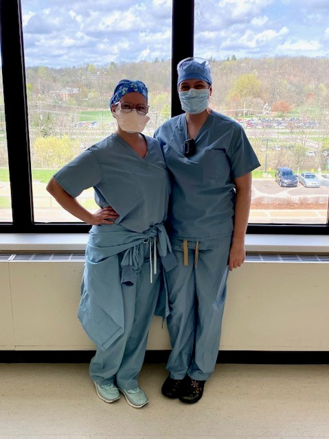 Two women in medical scrubs stand in front of a window with masks on.