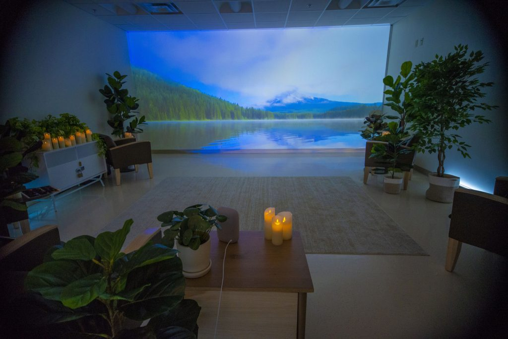 Room with a video screen at the front, candles and plants.