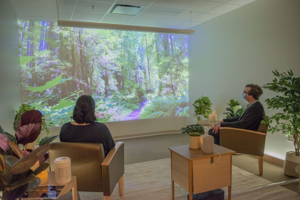 Two staff members wearing masks looking at a video screen.