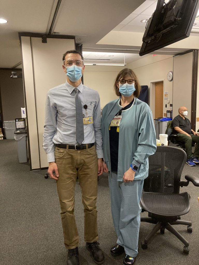 Man and woman standing next to one another wearing masks.