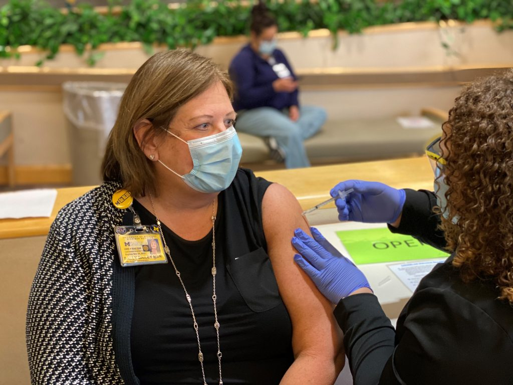 Woman in black shirt receives a vaccination from a nurse, who is sitting down.