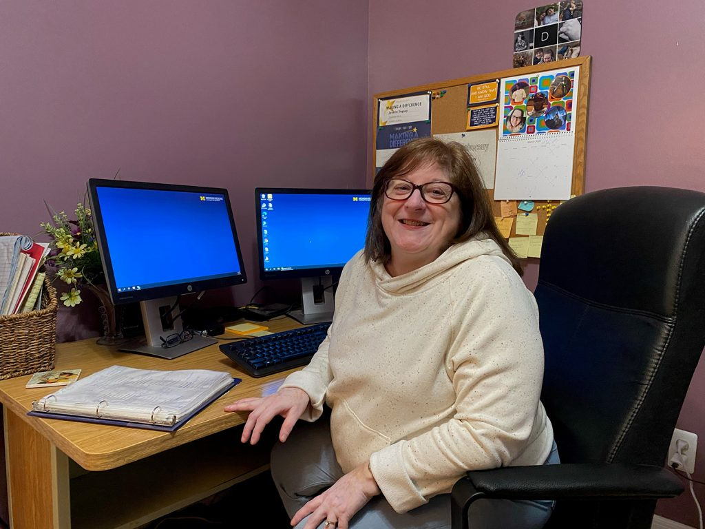 A woman sits in front of two computer monitors.