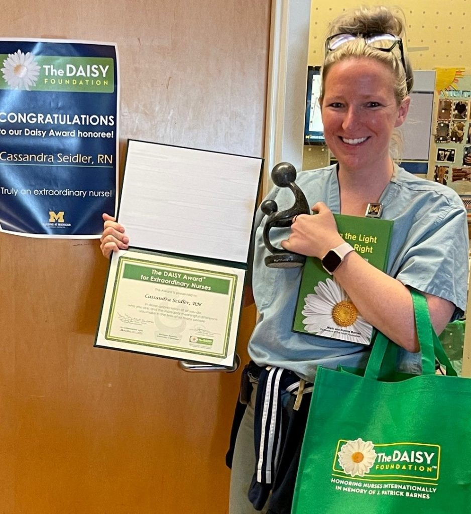 Nurse holds a trophy, a certificate and a green bag.