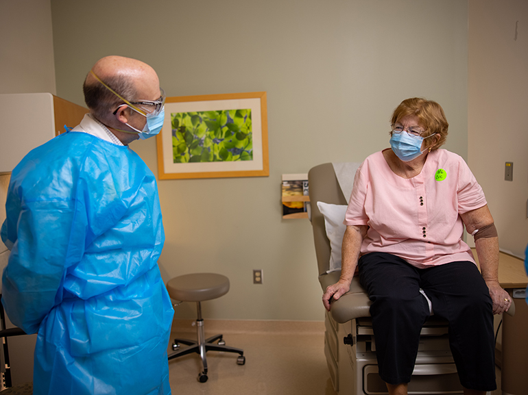 A woman in a mask sits on an exam table looking at a man in a mask.