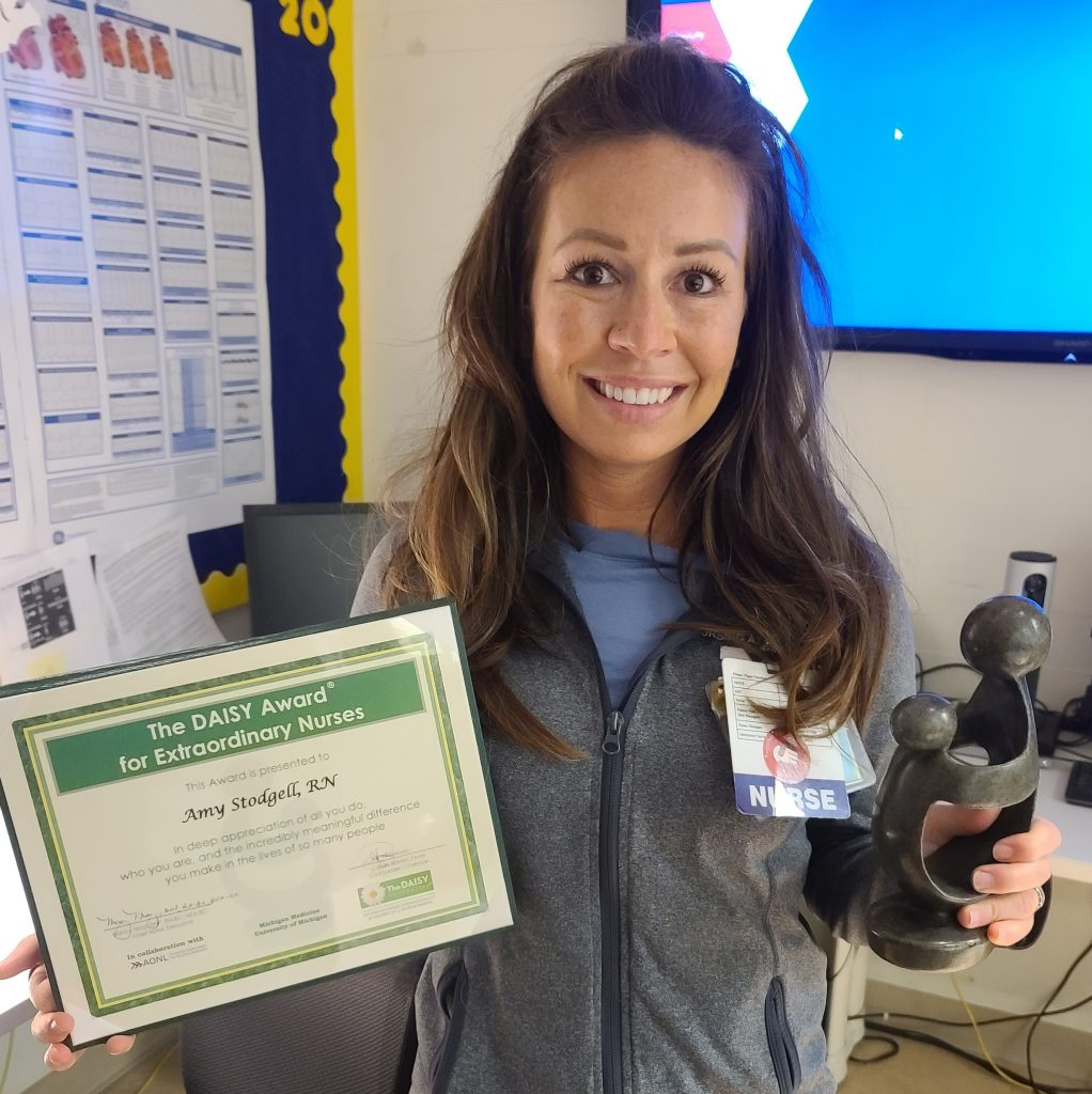Woman stands with an award certificate