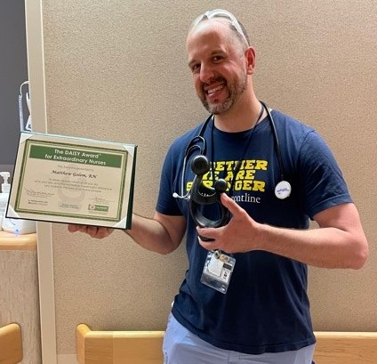 Man stands with an award certificate