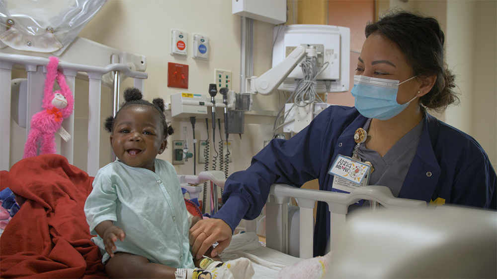 A nurse works at the bedside of a smiling young child.