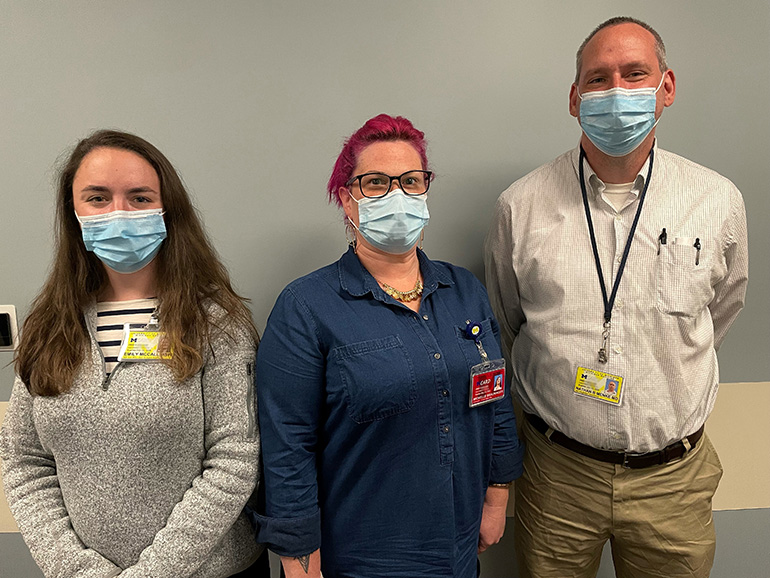 Two women and a man stand next to each other in a hallway wearing masks.