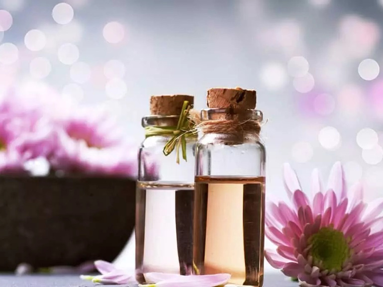 Two clear bottles of essential oils surrounded by pink flowers.