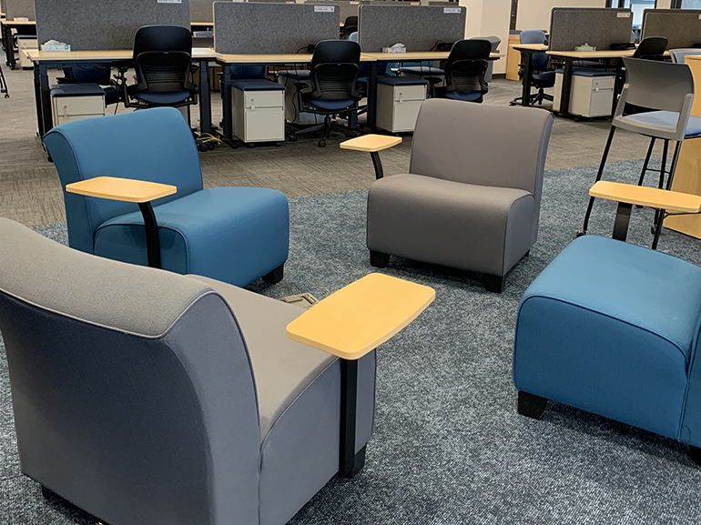 Four chairs with desks attached, with more workstations shown in the background.