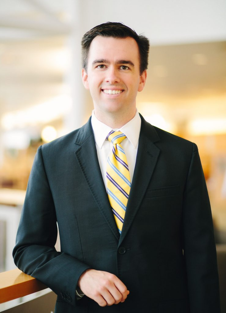 A man with dark hair and wearing a suit stands in the lobby of a hospital.