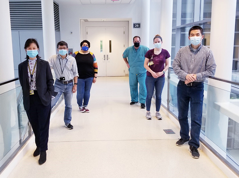 Six members of the Qi lab pose in a hallway wearing masks.
