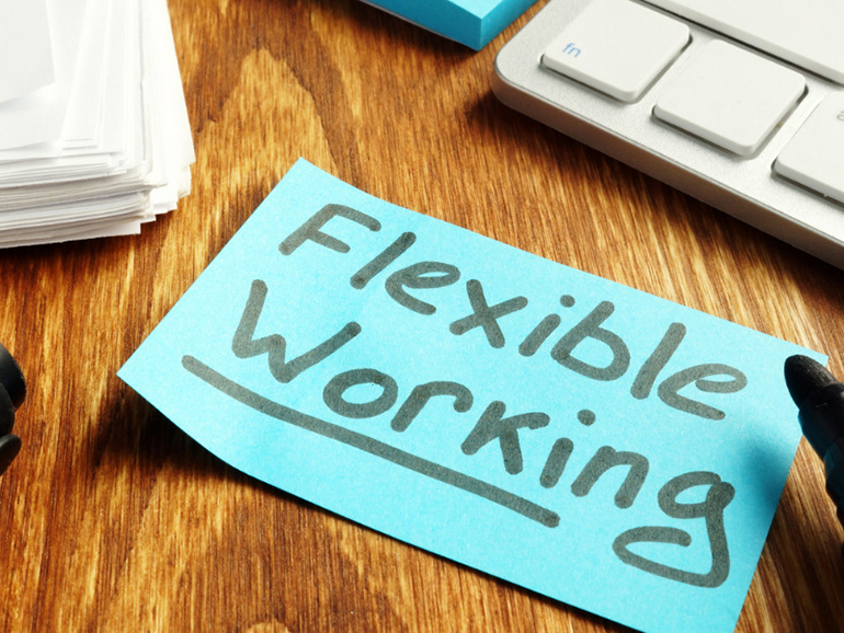 """Post-it Note saying """"Flexible Working"""" on a wooden table."""