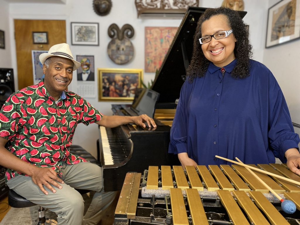 A man sits at a piano while a woman stands behind a vibraphone.