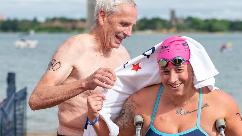Woman in swim cap gets dried off by older man with white hair.