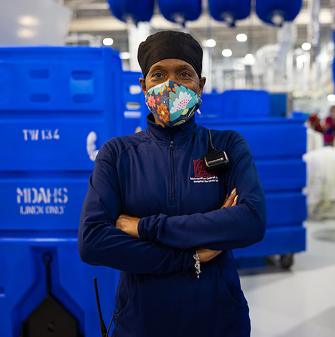 Employee in blue jacket standing in front of linen carts.