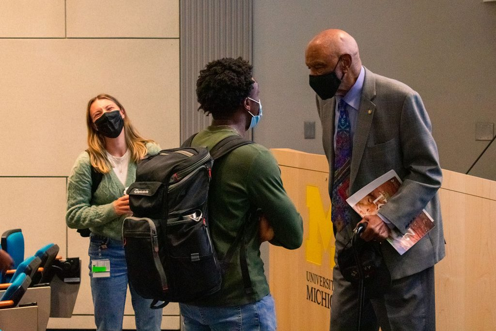 Man in suit and mask talks with two students.